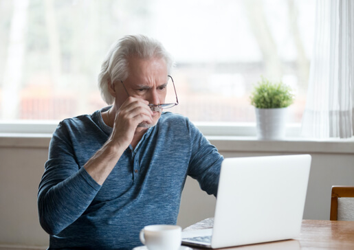 Hombre mirando una computadora con actitud de discernimiento